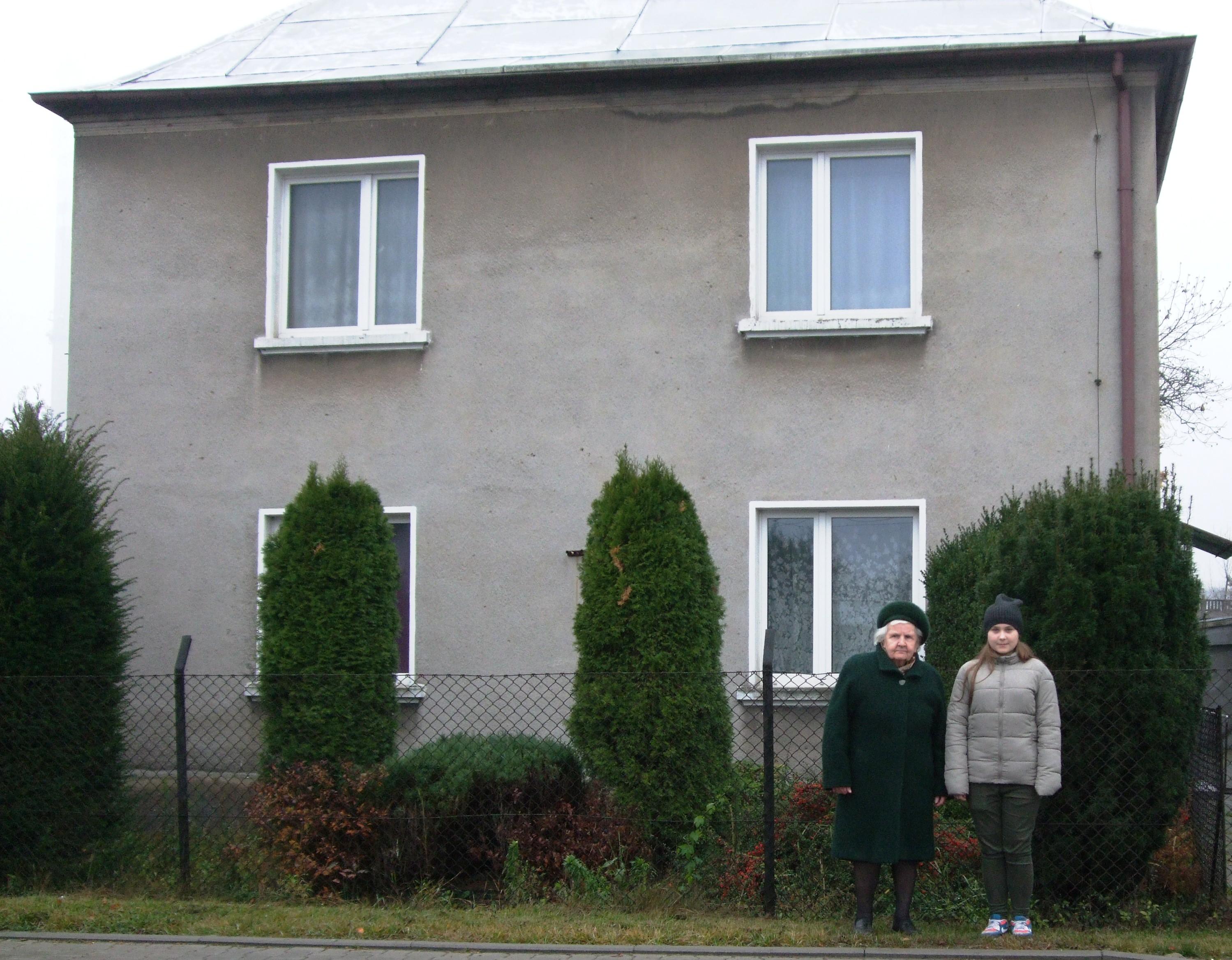 Marta Pilśniak z prawnuczką Klaudią na tle domu, z którego wysiedlono rodzinę. Zdjęcie z 2015 r.